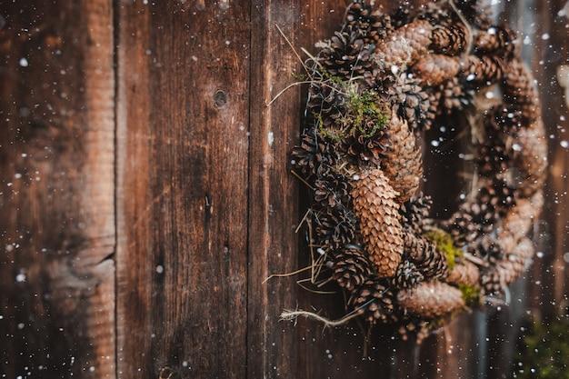 Świąteczny rustykalny wieniec szyszek na ciemnym brązowym tle drewnianych. koncepcja świąt bożego narodzenia i nowego roku.