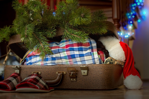 Świąteczny sen dziecka wewnątrz walizki. dziecko śpi obok ozdób choinkowych. urocza wakacyjna atmosfera. prezenty czekają.