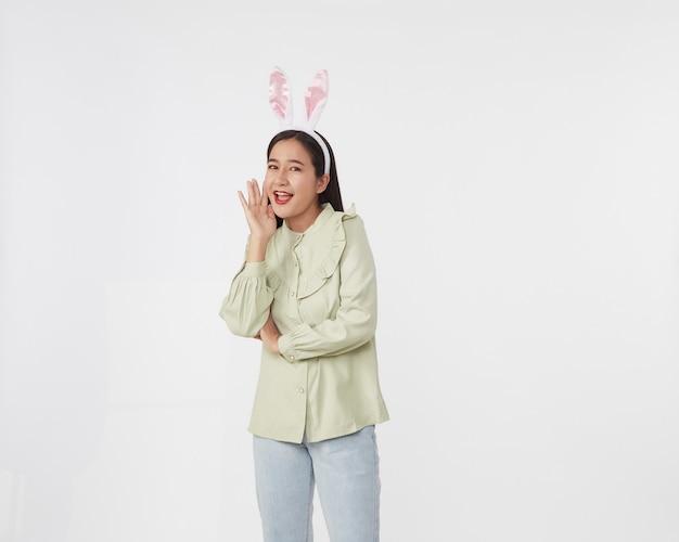 Świąteczny sezon na króliki i jajka. portret pięknej młodej kobiety azji w ucho zajączek z wielkanocą na białej powierzchni