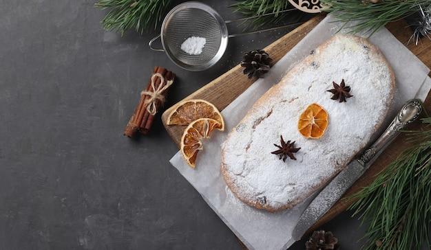 Świąteczny smaczny stollen z suchymi owocami, jagodami i orzechami na desce. tradycyjne niemieckie smakołyki.