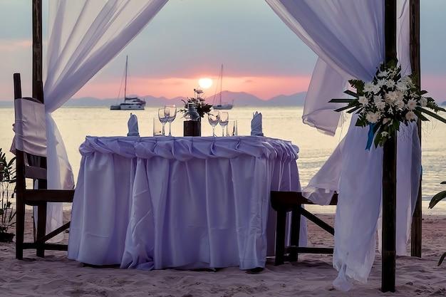 Świąteczny stół nad morzem udekorowany na romantyczną kolację zachód słońca jachty i góry