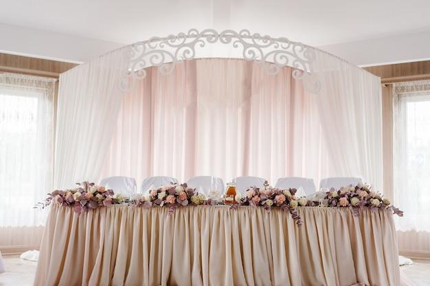 Świąteczny stół nowożeńców nakryty obrusem i ozdobiony kompozycją kwiatową