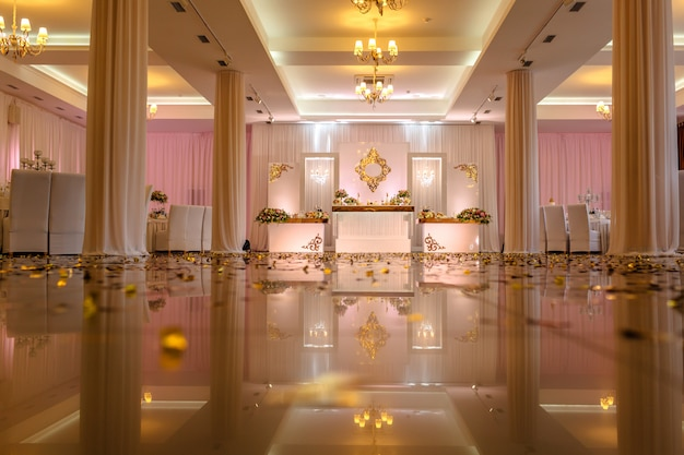 Świąteczny stół ozdobiony kompozycją białych, czerwonych i różowych kwiatów i zieleni w sali bankietowej.