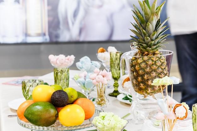 Świąteczny stół ozdobiony wazonami, owocami i ciastkami. w dekoracji stołu wykorzystano elementy florystyki.