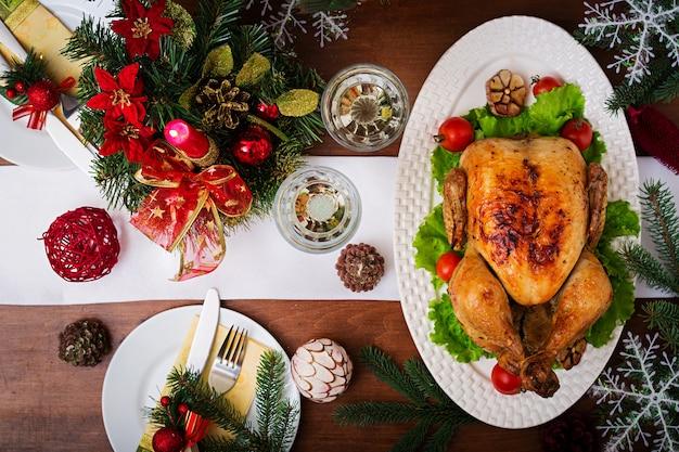 Świąteczny stół podany z indykiem, ozdobiony jasnym świecidełkiem i świecami