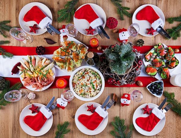 Świąteczny stół podawany jest z przystawką, udekorowaną jasnym blichtrem i świecami. nakrycie stołu. obiad świąteczny. leżał na płasko. widok z góry