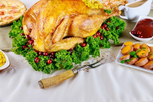 Świąteczny stół podawany z indykiem, ozdobiony jarmużem i żurawiną. koncepcja wakacje nowy rok.