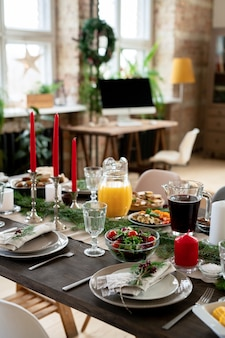 Świąteczny stół serwowany z domowym sokiem pomarańczowym, napojem jagodowym, sałatką ze świeżych warzyw, talerzami, świecami, szklankami, gałązkami iglastymi i widelcami