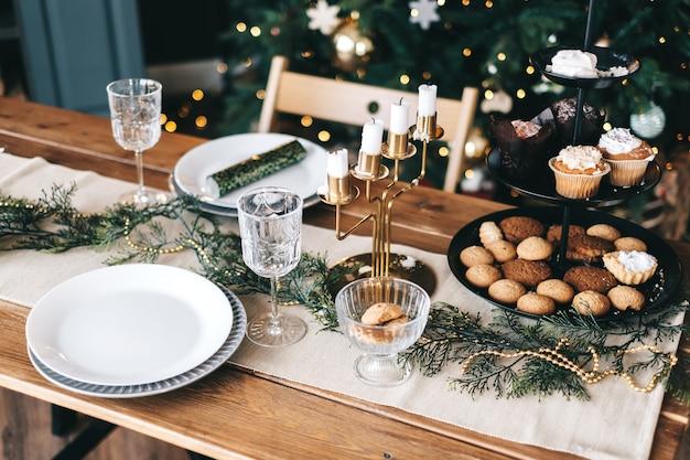 Świąteczny stół w kuchni z dużą choinką i dekoracjami.