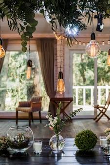 Świąteczny stół weselny z wiszącymi na sznurowadłach żarówkami garland of edison, ozdobionymi zielonymi gałązkami kwiatowymi. efekt ziarnisty