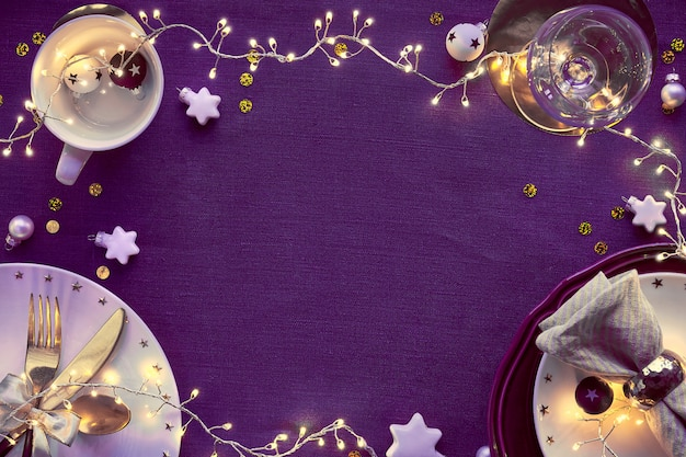 Świąteczny stół z białym talerzem i złotymi naczyniami oraz pozłacanymi dekoracjami. rozłożony na płasko, widok z góry na ciemnej lnianej tkaninie