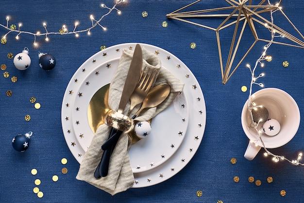 Świąteczny stół z białym talerzem i złotymi naczyniami oraz pozłacanymi dekoracjami.