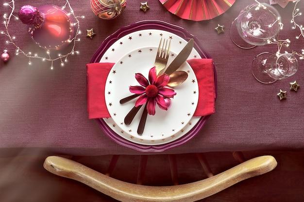 Świąteczny stół z naczyniami, ciemnoczerwonymi i złoconymi dekoracjami