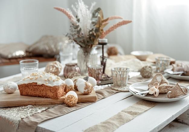 Świąteczny stół z piękną oprawą, dekoracyjnymi detalami, jajkami i ciastem wielkanocnym.