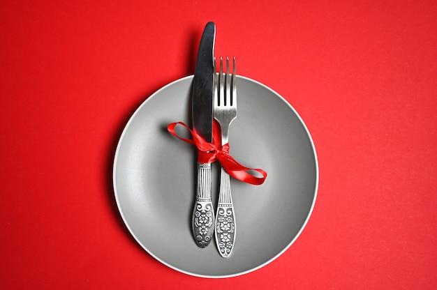 Świąteczny stół z talerzem, widelcem, nożem. widok z góry, kopia przestrzeń. na czerwonym tle.