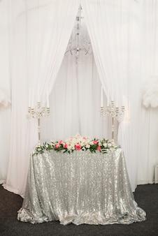 Świąteczny stół ze srebrnym obrusem z cekinami, dwoma świecznikami ze świecami, kompozycją kwiatów. dekoracje ślubne