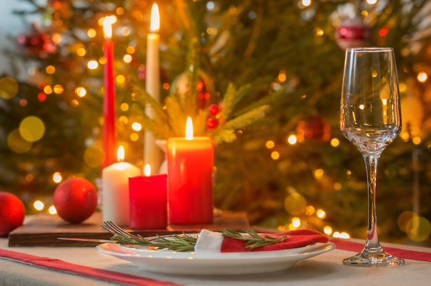 Świąteczny stół ze świecami na ścianie jodły