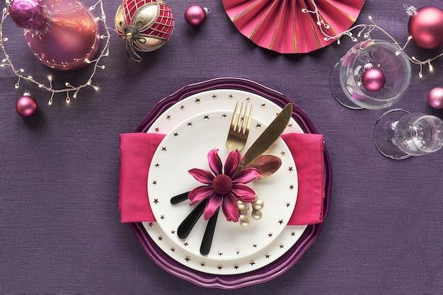 Świąteczny stół ze złotym, różowym i czerwonym dekorem na fioletowej lnianej tkaninie. talerze z kwiatami, naczyniami i kieliszkiem do wina.