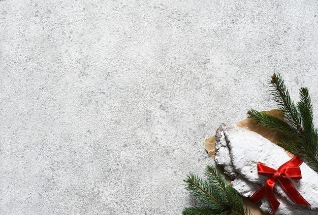 Świąteczny stollen z czerwoną wstążką jako prezent na betonowym stole.