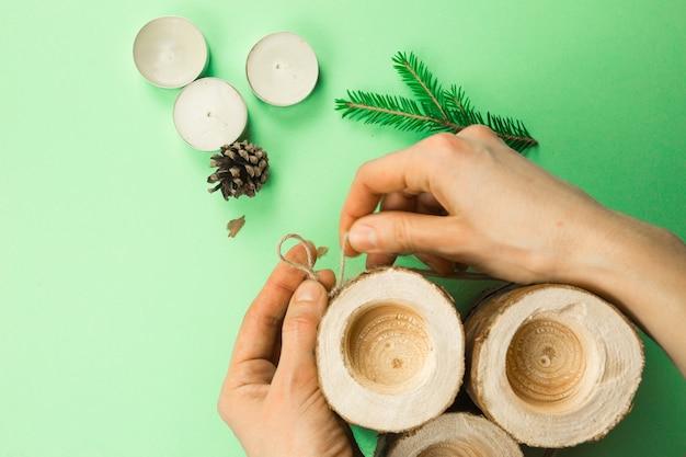Świąteczny świecznik diy wykonany z bali sosnowych, świec, liny rzemieślniczej, gałęzi jodłowych i szyszek. ręce zapinają i wiążą linę. instrukcja krok po kroku układanie na płasko, krok 3.