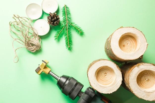 Świąteczny świecznik diy wykonany z bali sosnowych, świec, liny rzemieślniczej, gałęzi jodłowych i szyszek. wiertło to narzędzie do produkcji. wiercić dziury. instrukcja krok po kroku układanie na płasko, krok 2.