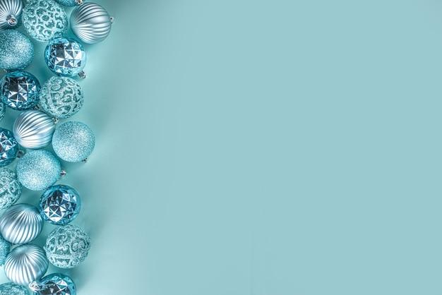 Świąteczny sztandar świąteczny, tło. monochromatyczny układ płaski z różnymi niebieskimi kulkami do dekoracji świątecznych na jasnoniebieskim tle, kopia miejsca z widokiem z góry, prosty wzór