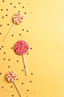 Świąteczny tło z lizakami i błyszczy na żółtym tle. wystrój urodzinowy lub imprezowy. obraz pionowy.