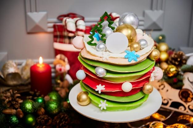 Świąteczny tort bananowy ozdobiony czekoladowymi bombkami i choinkami