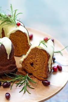 Świąteczny tort karmelowy, cutaway, ozdobiony białą czekoladą, żurawiną i rozmarynem na drewnianym stojaku. świąteczne wypieki. miękka selektywna ostrość. pionowo, z bliska.