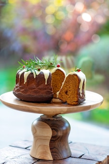 Świąteczny tort karmelowy, cutaway, ozdobiony białą czekoladą, żurawiną i rozmarynem na drewnianym stojaku. świąteczne wypieki. miękka selektywna ostrość. pionowy