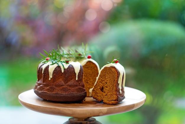 Świąteczny tort karmelowy, cutaway, ozdobiony białą czekoladą, żurawiną i rozmarynem na drewnianym stojaku. świąteczne wypieki. miękka selektywna ostrość.