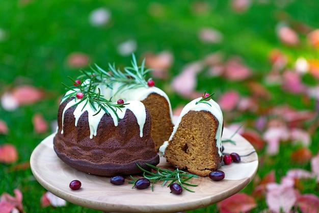 Świąteczny tort karmelowy, cutaway, ozdobiony białą czekoladą, żurawiną i rozmarynem na drewnianym stojaku wśród jesiennych liści. świąteczne wypieki. miękka selektywna ostrość. poziomy