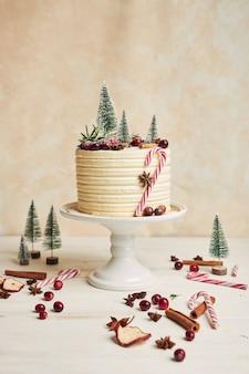 Świąteczny tort ozdobiony drzewami i jagodami oraz laskami cynamonu