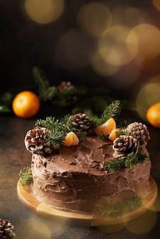 Świąteczny tort z czekoladą ozdobiony szyszkami i sosną