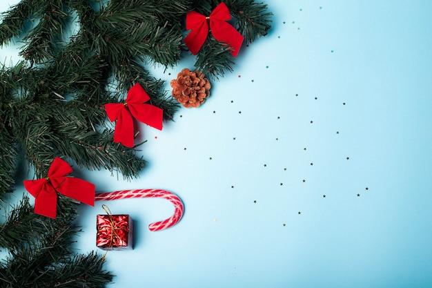 Świąteczny układ na niebieskim tle. miejsce na kopię z życzeniami świątecznymi. świerkowe gałęzie.