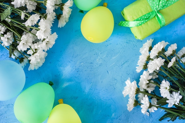 Świąteczny układ, urodziny. białe rumianki i żółto-niebieskie kulki na niebieskim drewnianym stole.