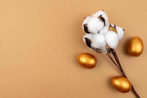 Świąteczny układ wielkanocny. bawełna kwiatek i złote jajka malowane na beżowym tle.