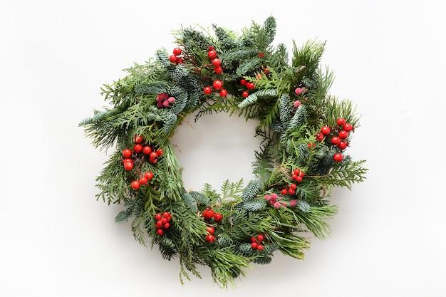 Świąteczny wieniec bożonarodzeniowy ze świeżych naturalnych gałązek świerkowych z czerwonymi jagodami ostrokrzewu