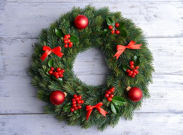 Świąteczny wieniec dekoracyjny z listkami jemioły na drewnianym tle