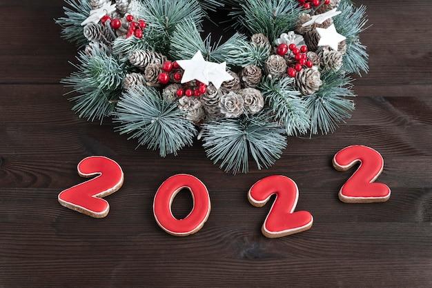 Świąteczny wieniec i piernik napis 2022. drewniane tło. ścieśniać.