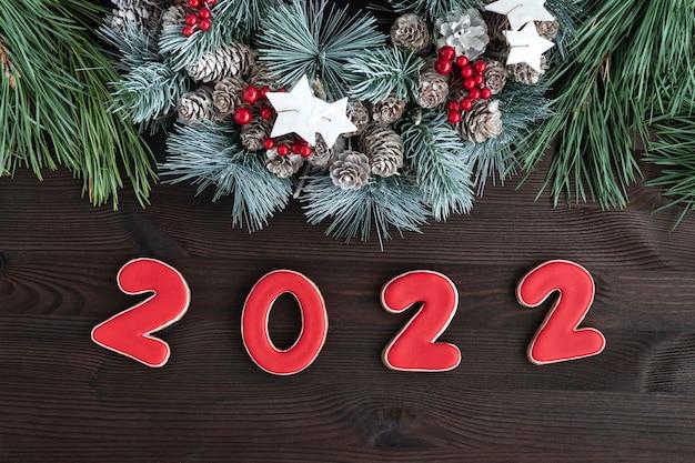 Świąteczny wieniec i piernik napis 2022. drewniane tło. ścieśniać
