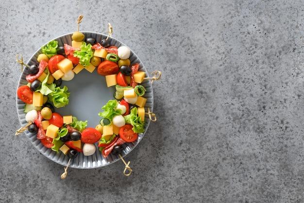 Świąteczny wieniec jadalny z świątecznych przekąsek, kanapek, pomidorów, oliwek, warzyw, serów.