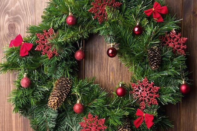 Świąteczny wieniec na rustykalnych drewnianych drzwiach wejściowych