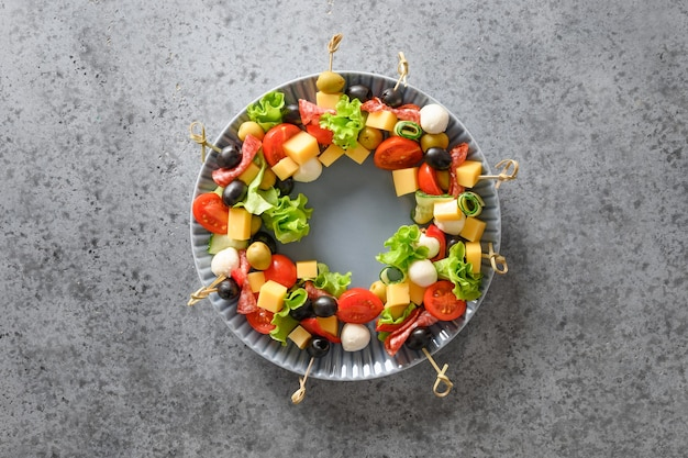 Świąteczny wieniec świątecznych przekąsek, kanapek, pomidorów, oliwek, warzyw, serów.