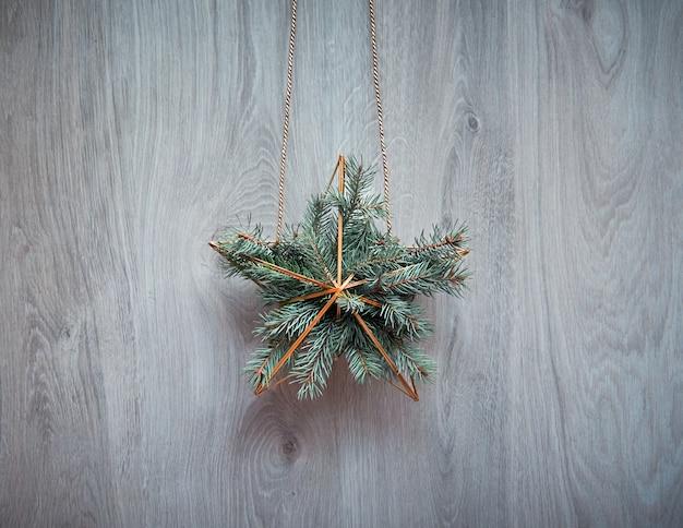 Świąteczny wieniec w kształcie złotej geometrycznej gwiazdy z gałązkami jodły zawieszony jest na rustykalnych drewnianych drzwiach, tradycyjny ornament świąteczny. minimalistyczny modny świąteczny wystrój bez marnotrawstwa.