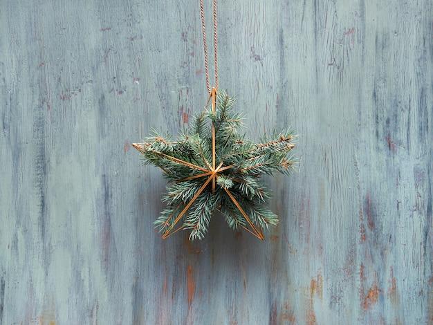 Świąteczny wieniec w kształcie złotej geometrycznej gwiazdy z gałązkami jodły zawieszony jest na rustykalnych drewnianych drzwiach, tradycyjny ornament świąteczny.