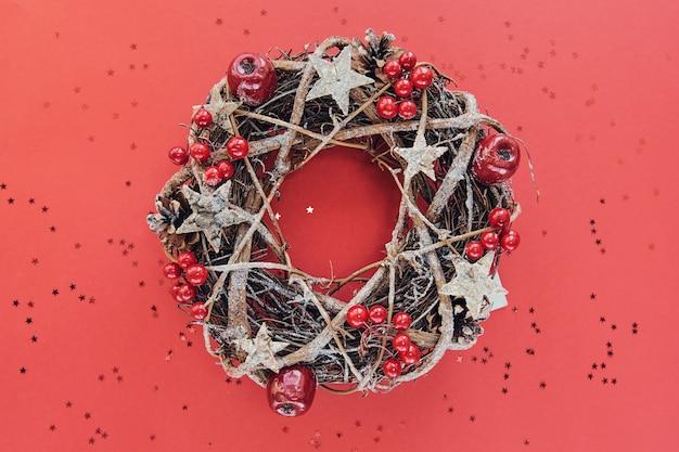 Świąteczny wieniec wykonany z gałęzi ozdobionych złotymi drewnianymi gwiazdami i bąbelkami czerwonych jagód na białym tle na czerwonym tle