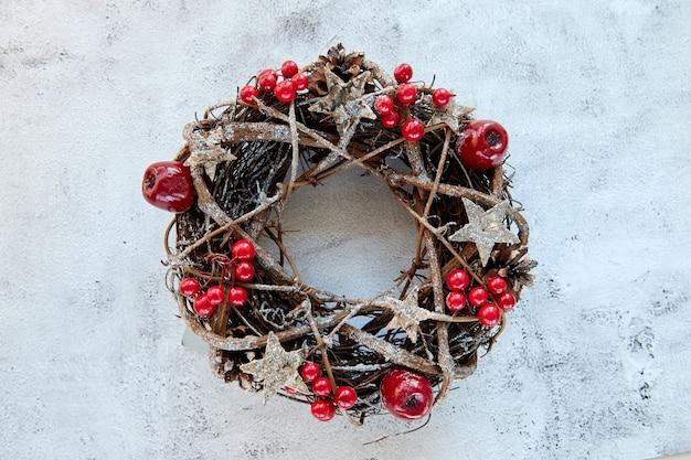 Świąteczny wieniec wykonany z gałęzi ozdobionych złotymi drewnianymi gwiazdkami i bąbelkami czerwonych jagód na cementowym tle