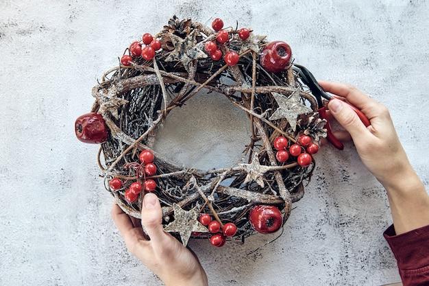 Świąteczny wieniec wykonany z gałęzi ozdobionych złotymi drewnianymi gwiazdkami i bąbelkami z czerwonych jagód. kreatywne hobby diy. wykonywanie ręcznie robionych ozdób choinkowych.