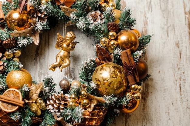 Świąteczny wieniec wykonany z jodły i ozdobiony złotymi tonami